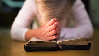 Stock - graphicstock-unrecognizable-woman-praying-with-hands-clasped-together-on-her-bible-close-up_BOghq3d8G-